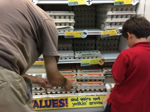 My son, very carefully checking the eggs just like the old man next to him.